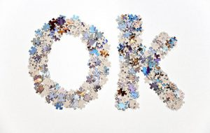The word OK written using two stacks of jigsaw puzzle pieces of different colors. It is captured separated on a white background for ease of use.