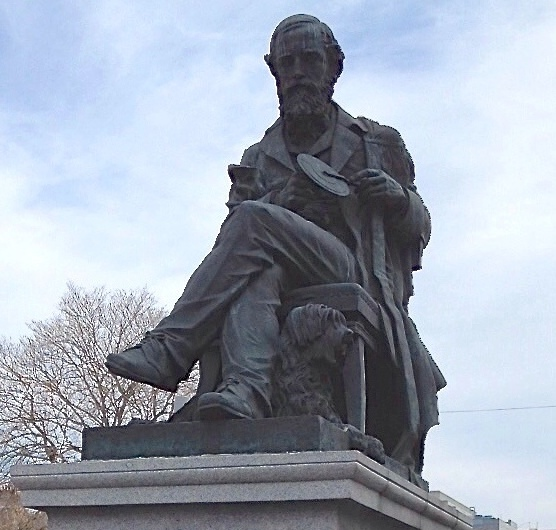 Estatua de James Clerk Maxwell en Edimburgo en la que puede verse sujetando uno de sus discos de color y acompañado de su perro Toby