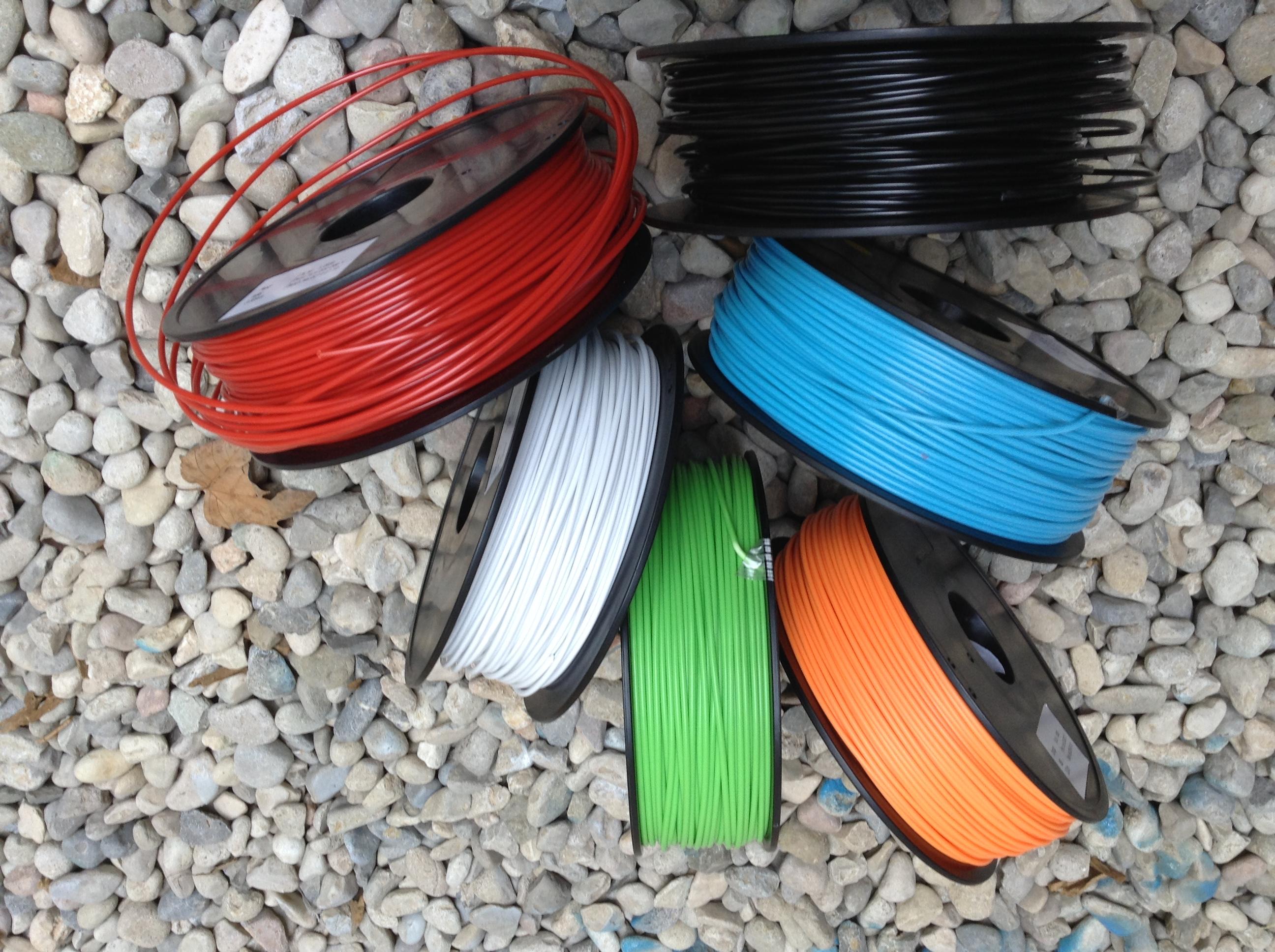 Imagen con los materiales de colores para impresión 3D. Negro, Rojo, Blanco, Cian, Naranja y Verde.