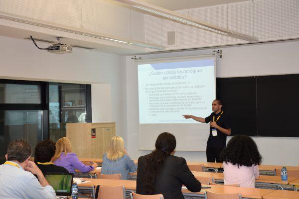 En un aula hay transparencias proyectadas sobre accesibilidad, se ve al ponente Jose Maria fernandez con varios alumnos impartiendo el taller
